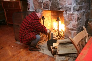 <b>Tending the fire in the hearth of pioneer home</b>
